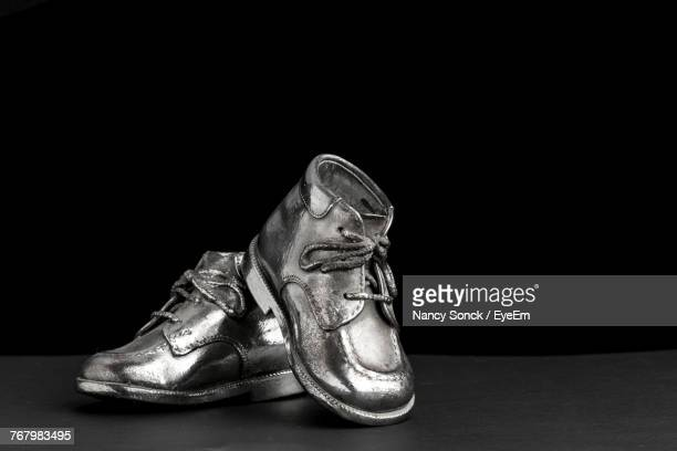 close-up of shoes on table over black background - silver shoe stock photos and pictures
