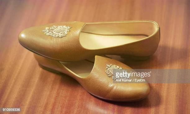 close-up of shoes on table - gold shoe stock photos and pictures