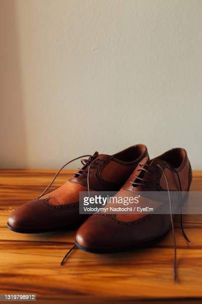 close-up of shoes on wooden floor - lino stock pictures, royalty-free photos & images