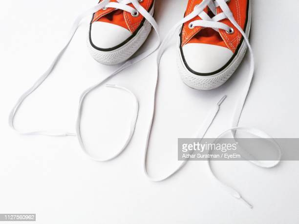 close-up of shoes over white background - orange shoe stock photos and pictures