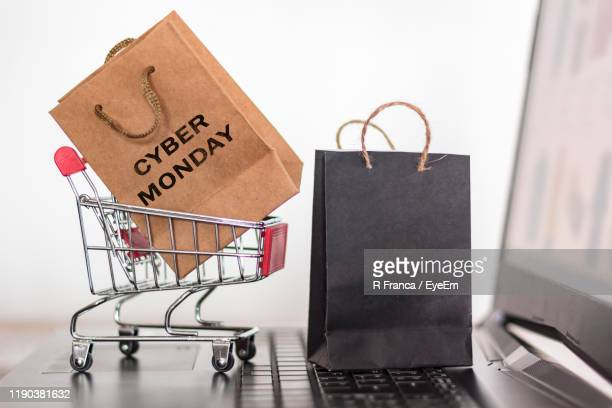 close-up of shopping bag in small shopping cart on laptop against white background - cyber monday stock pictures, royalty-free photos & images
