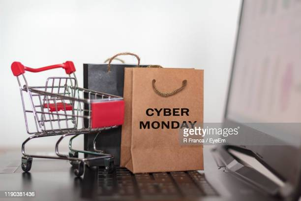 close-up of shopping bags by small shopping cart on laptop against white background - cyber monday stock pictures, royalty-free photos & images