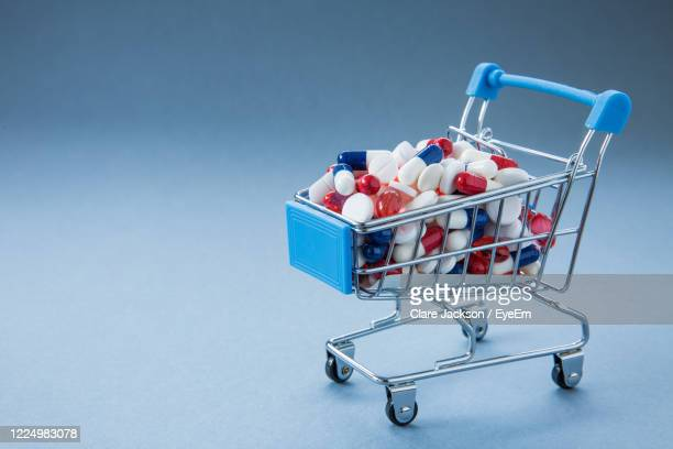 close-up of shopping cart against blue background with antibiotic resistant drugs - panic buying stock pictures, royalty-free photos & images
