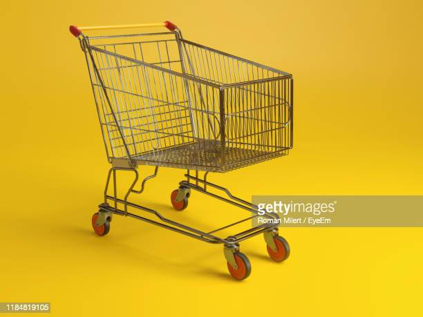 close-up of shopping cart against yellow background - shopping trolley stock pictures, royalty-free photos & images