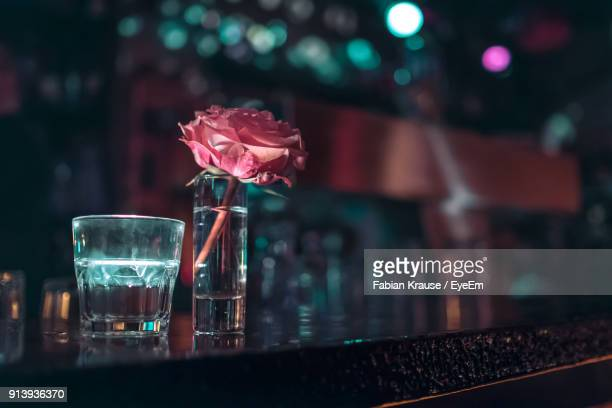 close-up of shot glass with rose on bar counter - comptoir de bar photos et images de collection