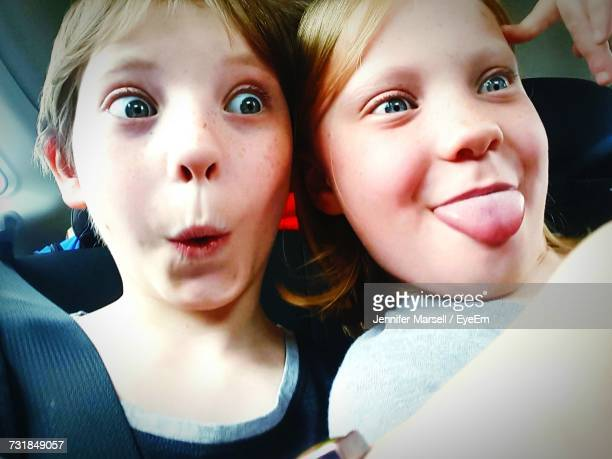 Close-Up Of Siblings Making Face While Sitting In Car