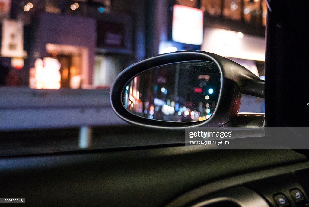 Close-Up Of Side-View Mirror Against Illuminated Buildings At Night : Stock Photo
