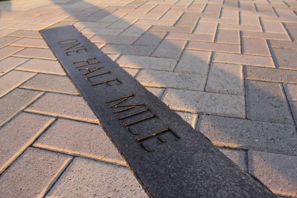 """Close-up of sidewalk """"One Half Mile"""" distance marker"""