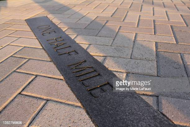 "close-up of sidewalk ""one half mile"" distance marker - マイル ストックフォトと画像"