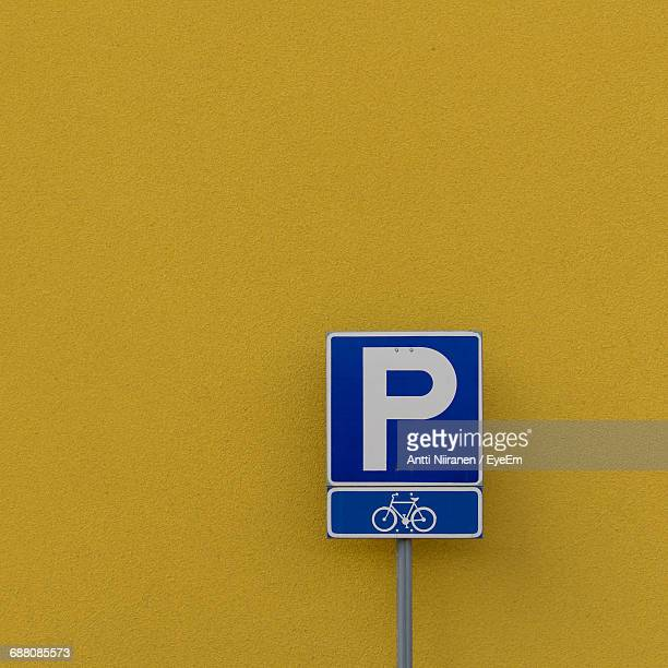 Close-Up Of Sign Board Against Yellow Wall
