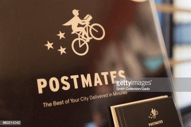 Closeup of sign for the popular appbased food and supplies deliver service Postmates in the Gourmet Ghetto neighborhood of Berkeley California...