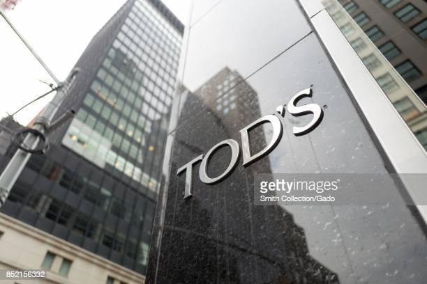 Close-up of sign with logo for Tod's upscale boutique shoe store, with building visible in the background, on Madison Avenue in Manhattan, New York...