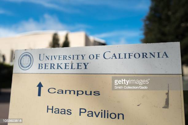 Closeup of sign with text reading University of California Berkeley with arrow directing visitors to the campus of UC Berkeley in Berkeley California...