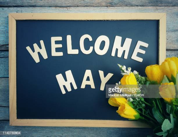 close-up of sign with yellow artificial flowers on table - mois de mai photos et images de collection