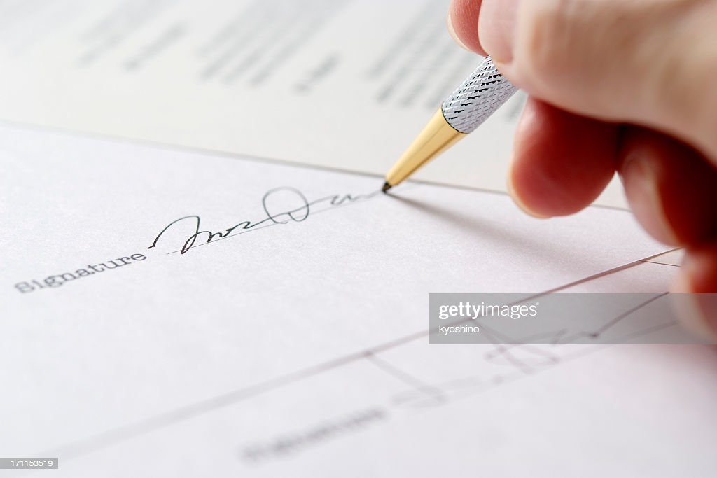 Close-up of signing a contract with shallow depth of field : Stock Photo