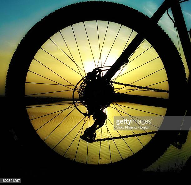 close-up of silhouette bicycle wheel at lakeshore during sunset - 変速ギア ストックフォトと画像