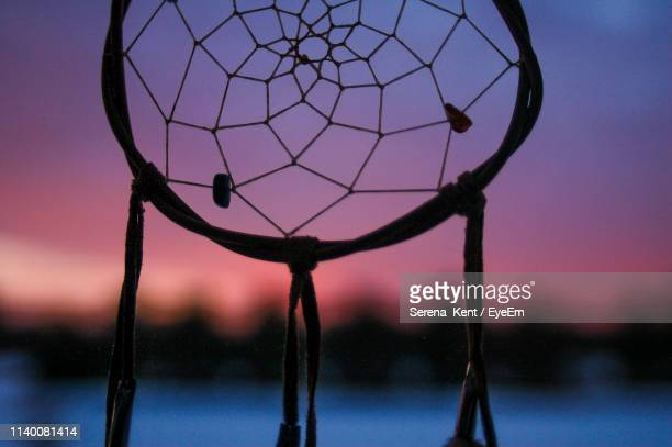 close-up of silhouette dreamcatcher against sky during sunset - dreamcatcher stock pictures, royalty-free photos & images