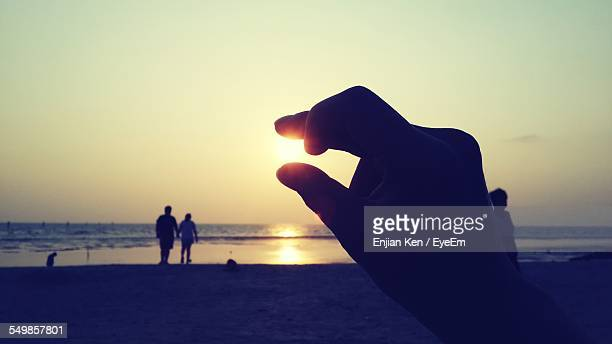 Close-Up Of Silhouette Fingers Trying To Hold Sun
