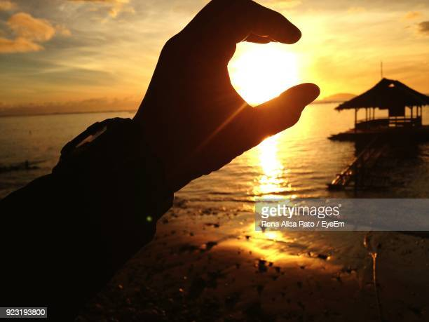 Close-Up Of Silhouette Hand Covering Sun On Beach During Sunset