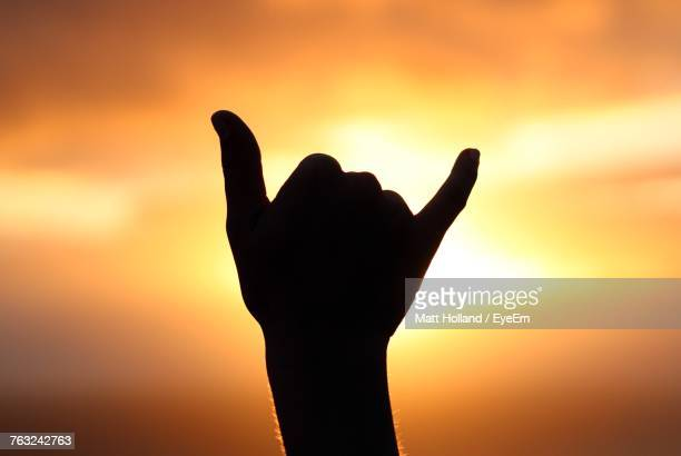 Close-Up Of Silhouette Hand Gesturing Shaka Sign Against Orange Sky