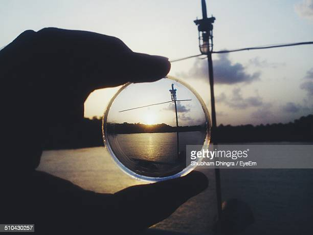 close-up of silhouette hand holding lens at calm sea against sky - panjim stock photos and pictures