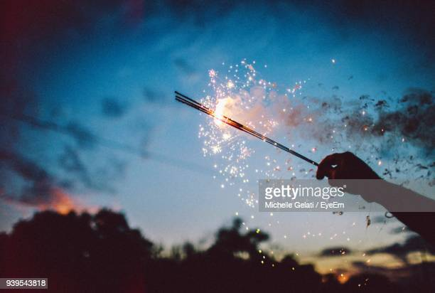 Close-Up Of Silhouette Hand Holding Sparklers Against Sky At Night