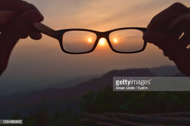 Close-Up Of Silhouette Hands Holding Eyeglasses Against Sun Against Sky During Sunset