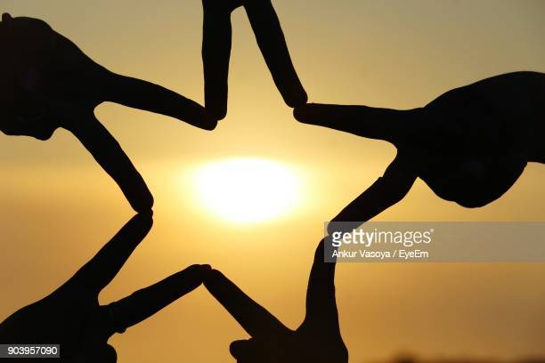 Close-Up Of Silhouette Hands Making Star Shape Against Sky During Sunset
