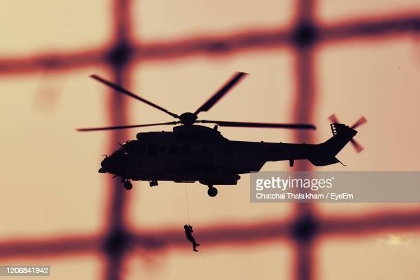 close-up of silhouette helicopter against sky - chatchai thalaikham stock pictures, royalty-free photos & images