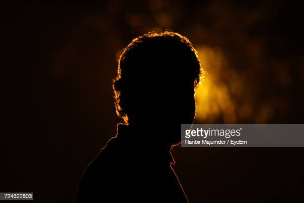 close-up of silhouette person against black background - nicht erkennbare person stock-fotos und bilder