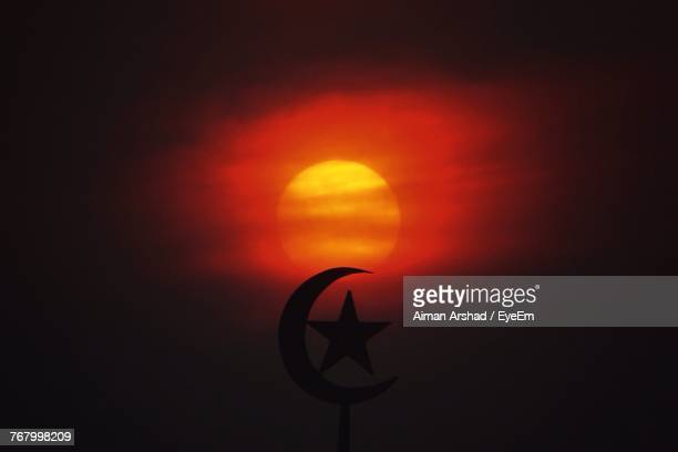 Close-Up Of Silhouette Star And Crescent Against Orange Sky