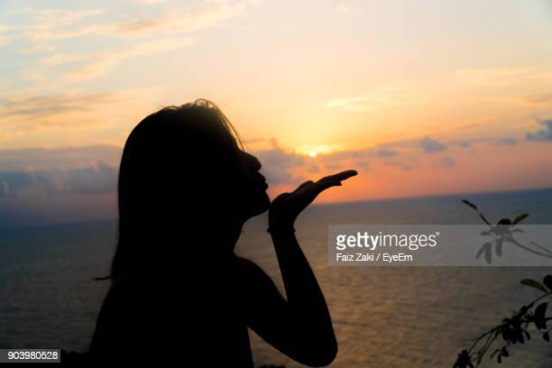 Close-Up Of Silhouette Woman Blowing Kiss By Sea Against Sky During Sunset