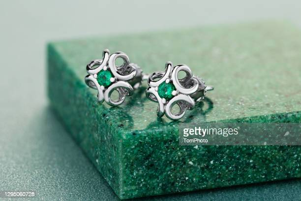 close-up of silver earrings with emeralds on green background - earring stock pictures, royalty-free photos & images