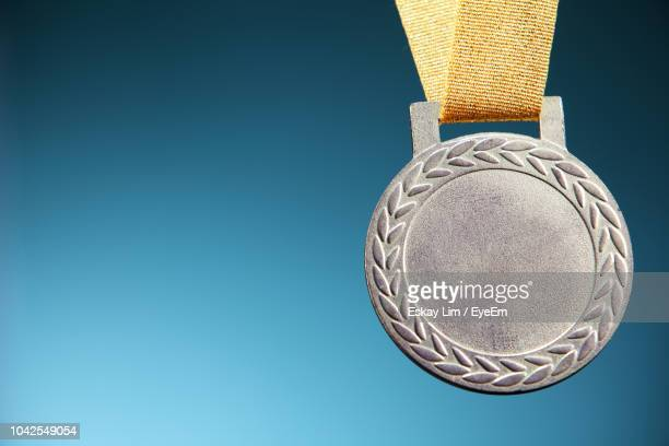 Close-Up Of Silver Medal Against Blue Background