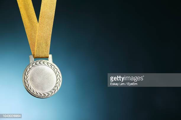 close-up of silver medal against blue background - second place stock pictures, royalty-free photos & images