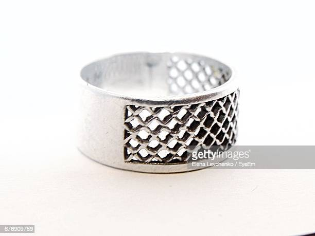 Close-Up Of Silver Ring Against White Background