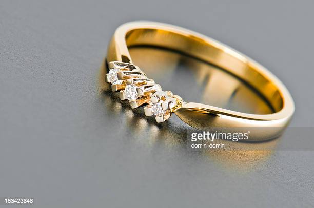 Close-up of single golden ring with diamonds against solid gray