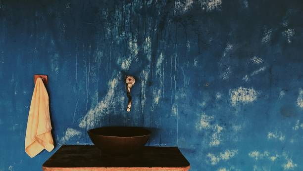 Close-Up Of Sink Below Faucet On Blue Wall
