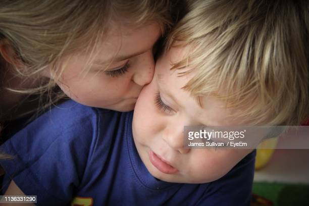 close-up of sister kissing brother at home - arabian girl kissing stock photos and pictures