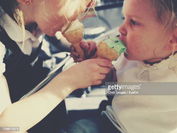 Close-Up Of Sisters Feeding Ice Cream To Each Other
