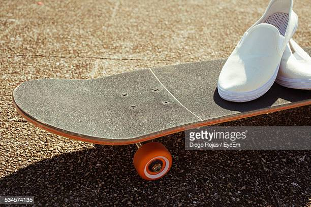Close-Up Of Skateboard With Shoes On Street
