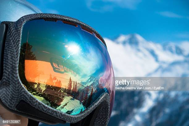 Close-Up Of Ski Goggles By Snow Covered Mountains