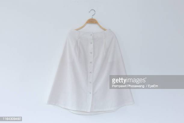 close-up of skirt hanging from coathanger against white background - スカート ストックフォトと画像
