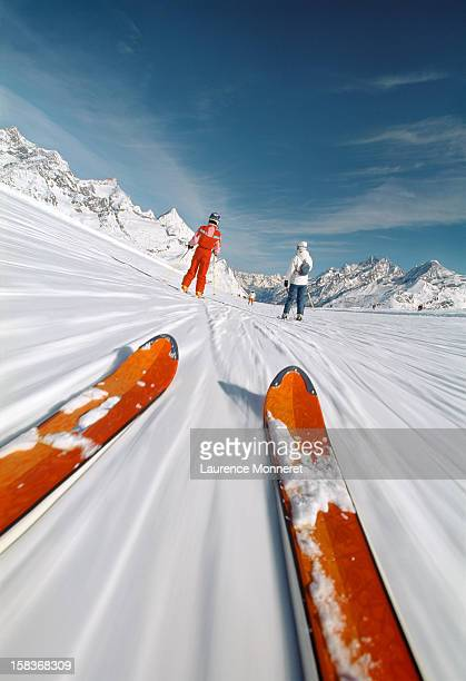 Close-up of skis, following skiiers on a ski slope