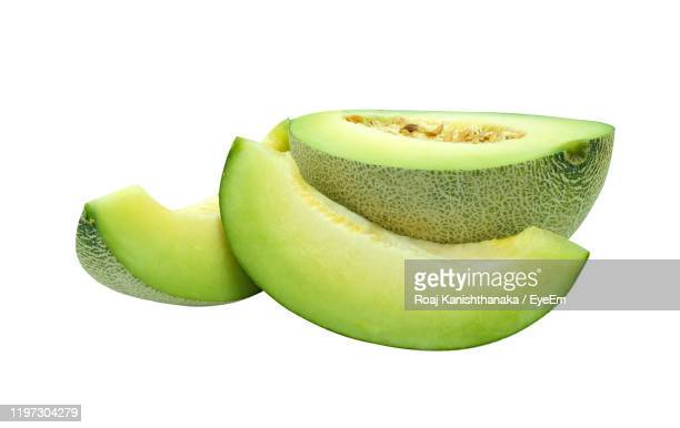 close-up of slice green melon fruit white background - muskmelon stock pictures, royalty-free photos & images