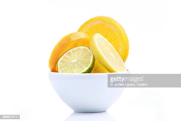 Close-Up Of Sliced Citrus Fruits In Bowl On White Background