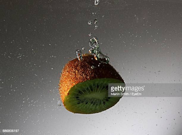 Close-Up Of Sliced Kiwi Fruit In Water Against Gray Background