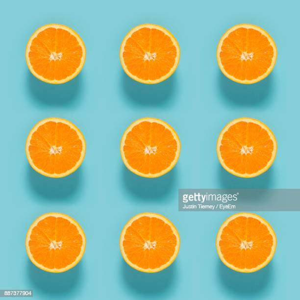 close-up of sliced orange fruits on blue background - orange imagens e fotografias de stock