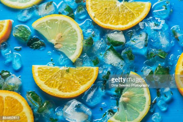 Close-up of sliced oranges and lemons on a blue background with ice cubes
