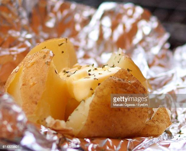 close-up of sliced potato with butter on foil - ジャガイモ料理 ストックフォトと画像